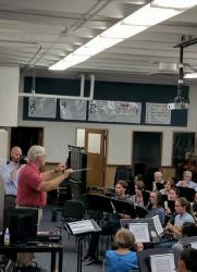 Charles Craig leading the students and alumni during rehearsal